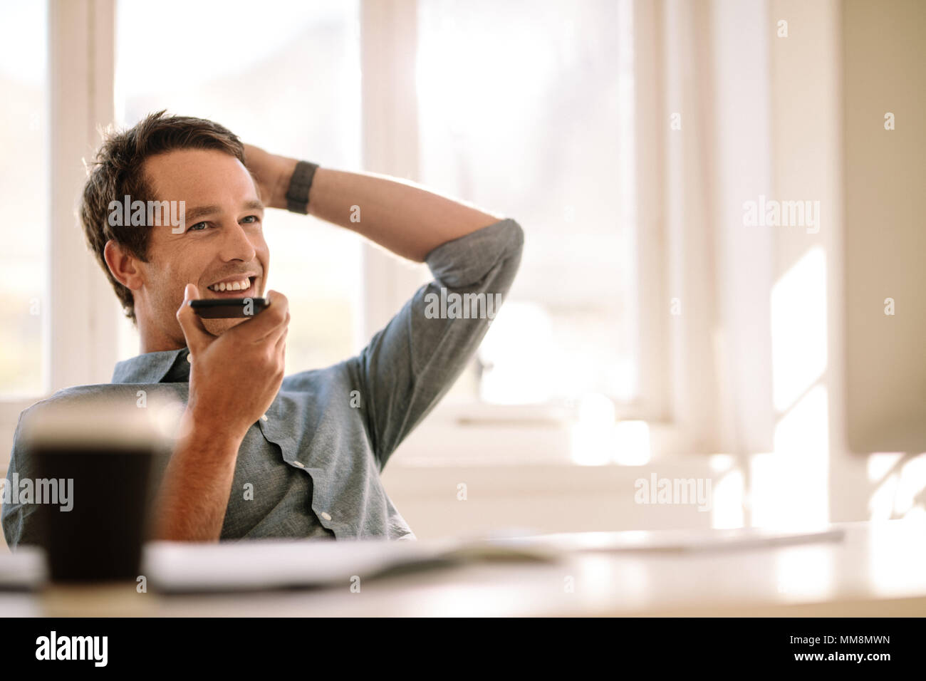 Man holding mobile phone in hand and talking on loudspeaker looking away. Businessman working from the comfort of his home. Stock Photo