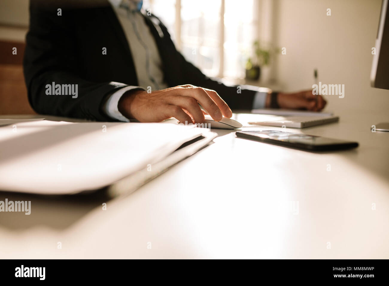 Side view of businessman operating computer sitting at his table. Entrepreneur working on computer sitting at home. - Stock Image