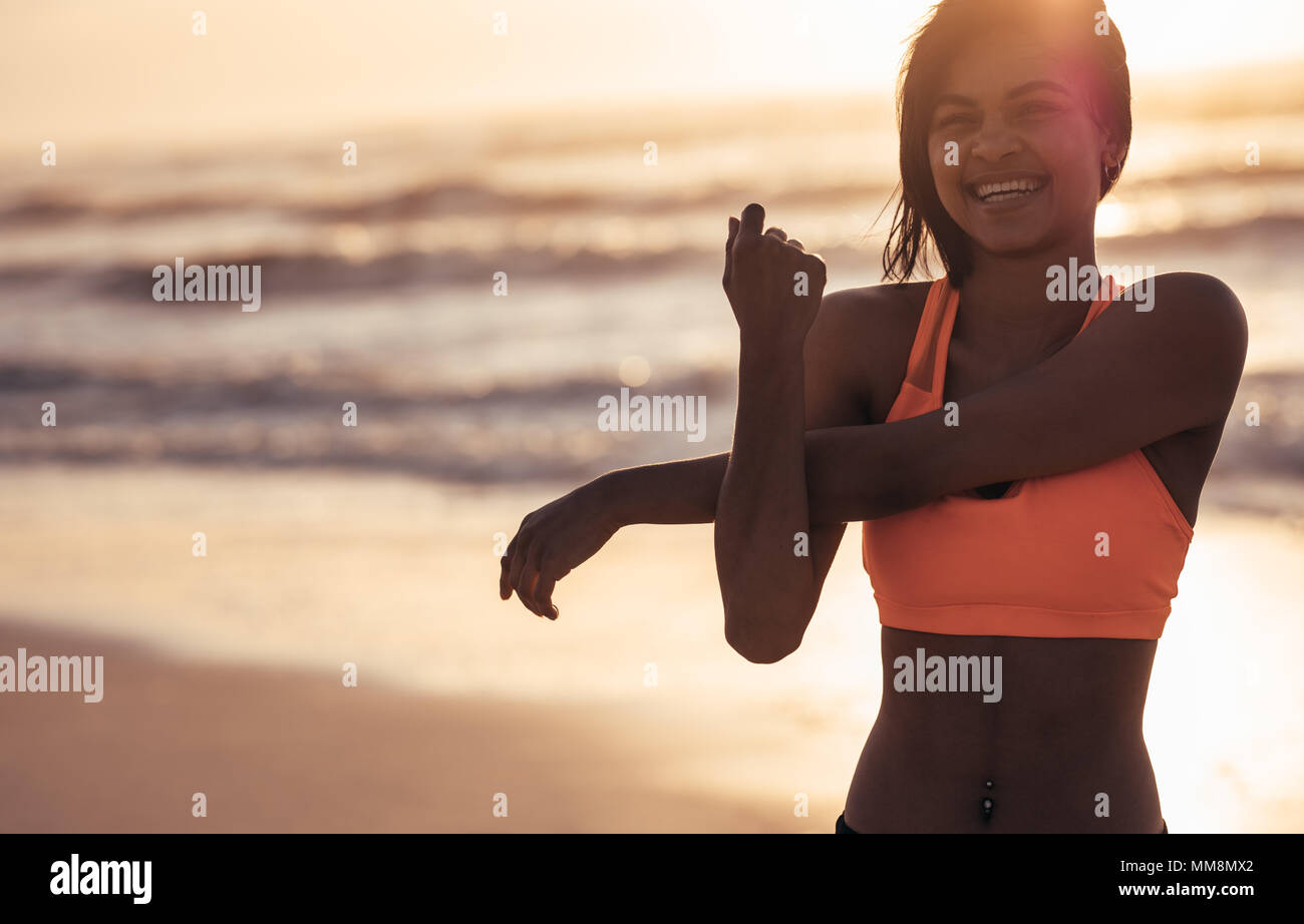 Smiling woman stretching arms at the sea shore. Female athlete doing warm up workout at the beach. - Stock Image