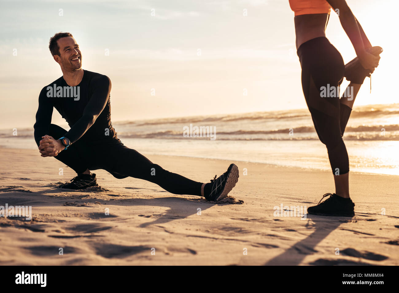 Young people exercising on the beach in morning. Runner stretching and warming up along the sea shore and having a chat. - Stock Image