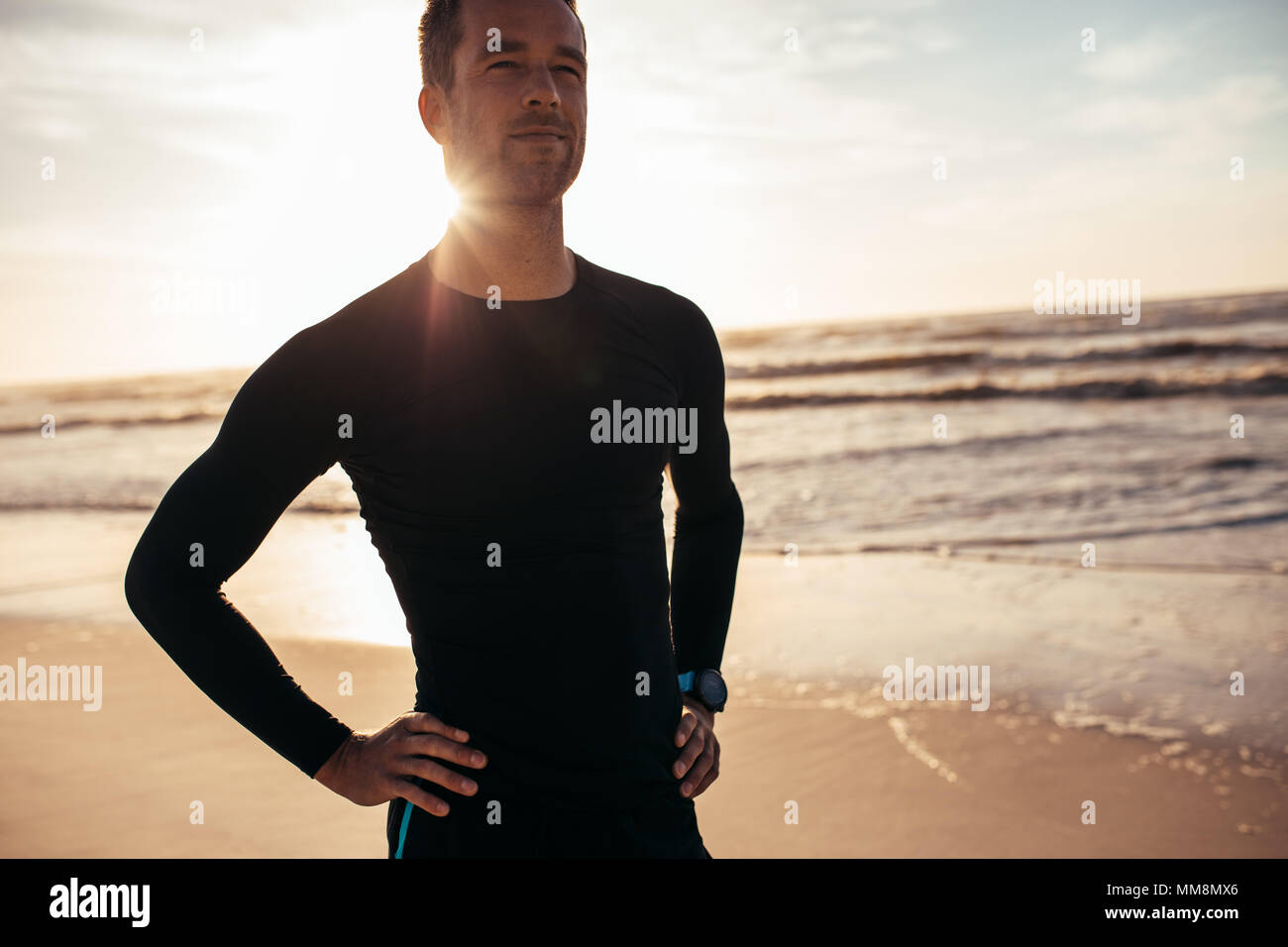 Portrait of confident male athlete standing on the beach. Man in sportswear along the sea shore in morning. Stock Photo