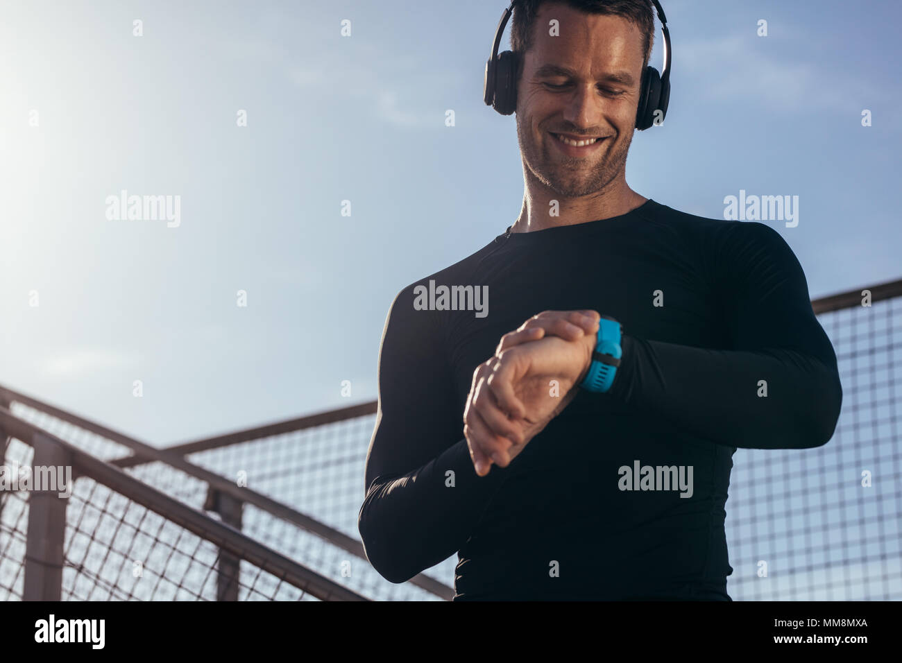 Man standing outdoors with headphones using a smartwatch to monitor his progress. Male athlete resting and checking his performance on fitness smartwa - Stock Image