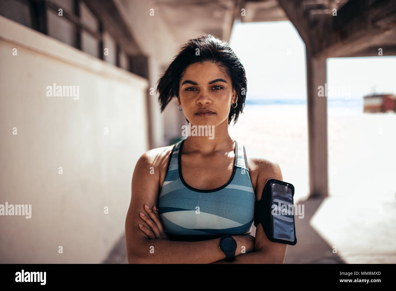 Portrait of confident woman athlete standing outdoors with her arms crossed and looking at camera. Female with mobile phone on armband taking a break  - Stock Image