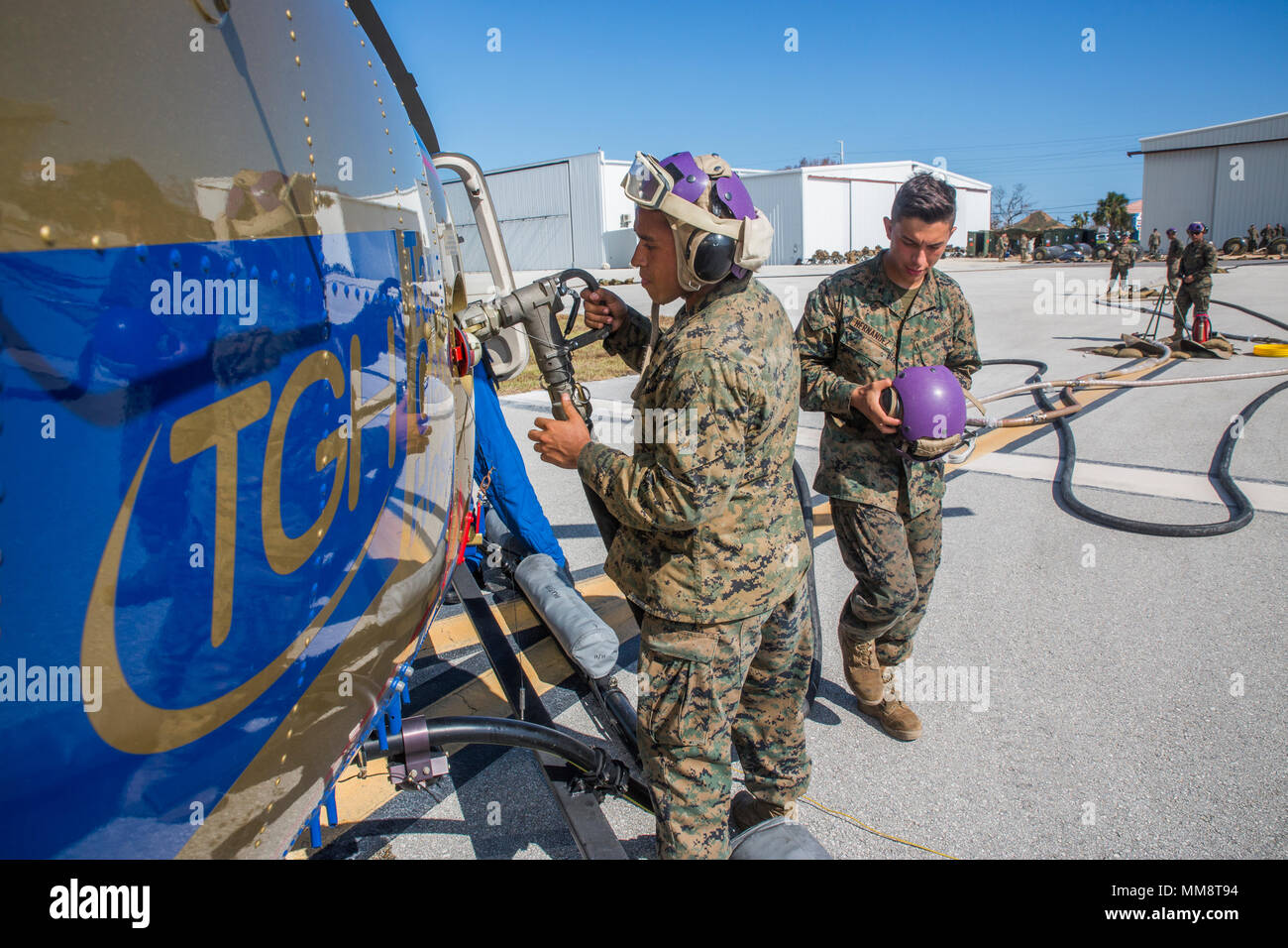 Lance Cpl. Sergio Hernandez (left), a bulk fuel specialist, and Pfc. Nicolas Hernandez (right), a Motor-T operator, both with Marine Wing Support Squadron 473, 4th Marine Aircraft Wing, Marine Forces Reserve, refuel a helicopter from Tampa General Hospital at The Florida Keys Marathon International Airport, in Marathon, Fla. Sept. 14, 2017. Marines with MWSS-473 established a forward arming and refueling point to provide support to federal, state and local agencies, to assist in their search and rescue operations in wake of Hurricane Irma. (U.S. Marine Corps photo by Lance Cpl. Niles Lee/Relea Stock Photo