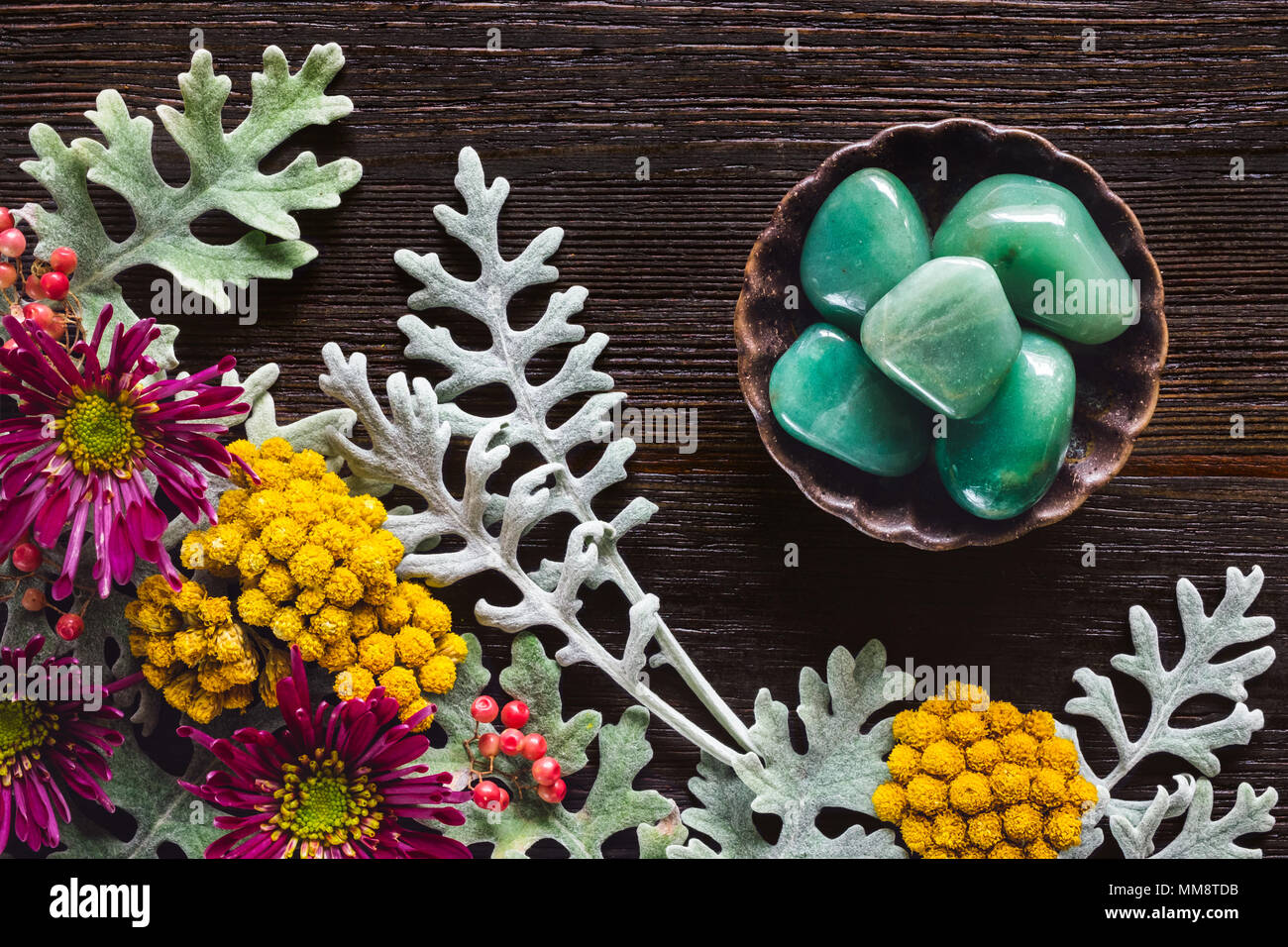 Green Aventurine Stones with Dusty Miller, Clustered Everlasting and Chrysanthemums on Dark Table with Space for Copy - Stock Image