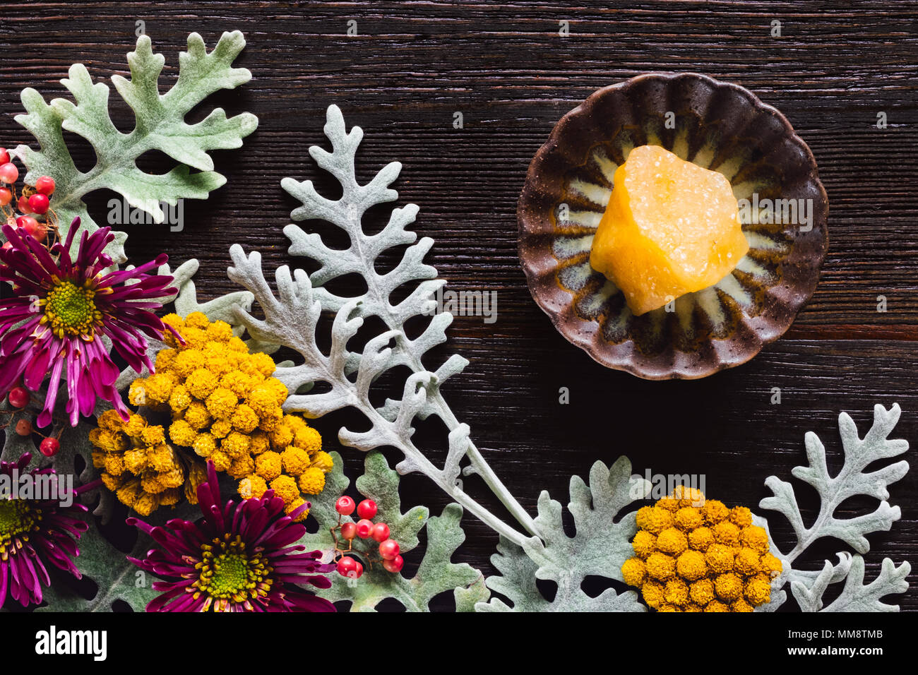 Yellow Aventurine Crystal with Dusty Miller, Clustered Everlasting and Chrysanthemums on Dark Table with Space for Copy - Stock Image