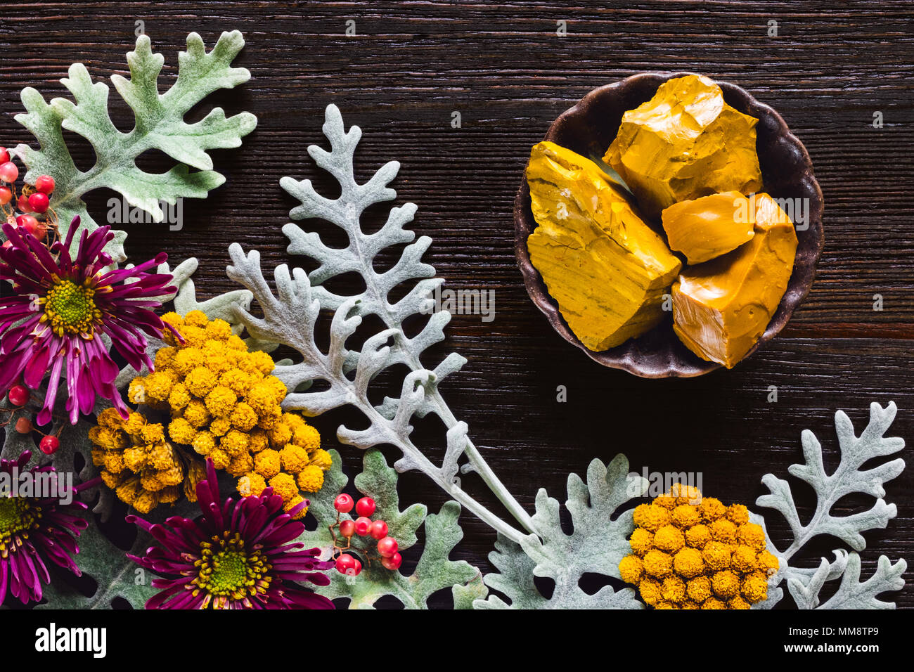 Yellow Jasper Stones with Dusty Miller, Clustered Everlasting and Chrysanthemums on Dark Table with Space for Copy - Stock Image