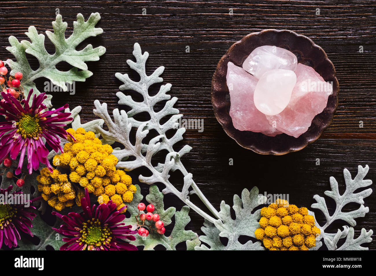 Rose Quartz Crystals with Dusty Miller, Clustered Everlasting and Chrysanthemums on Dark Table with Space for Copy - Stock Image