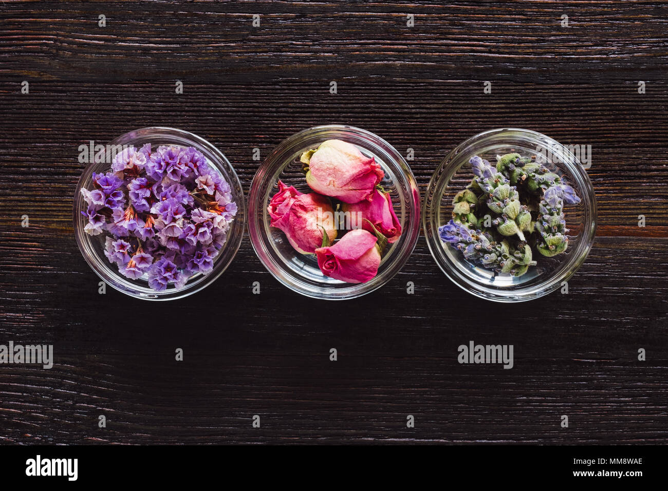 Bowls of Dried Lavender, Rose, and Sea Lavender Aligned and Centered on Dark Table with Space for Copy - Stock Image