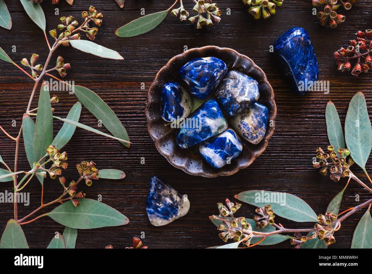 Ceramic Bowl of Sodalite on Dark Table with Eucalyptus. Stock Photo