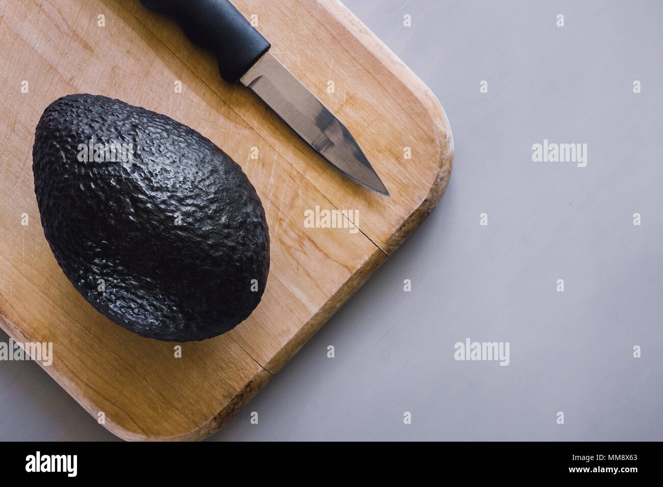 Unopened Avocado on Cutting Board with Space for Copy - Stock Image