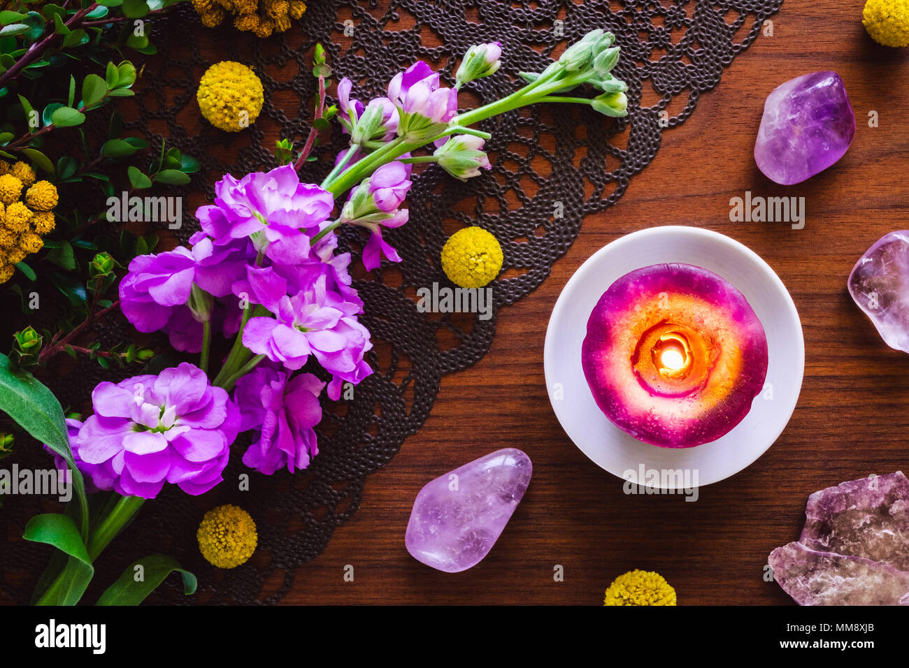Purple Stones, Flowers and Candle on Teak Table Stock Photo