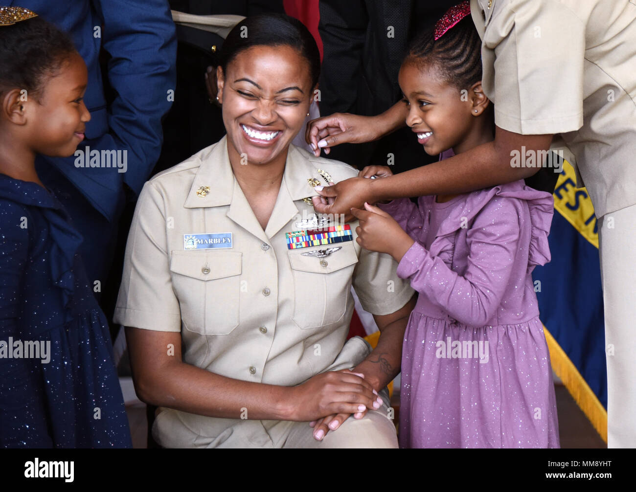 GARDEN CITY, New York (Sept. 15, 2017) Chief Navy Counselor Danielle Marbley, a native of Newark, New Jersey assigned to Navy Recruiting District New York, having her new anchors pinned on by her daughters during a chief petty officer pinning ceremony at the Cradle of Aviation Museum. (U.S. Navy photo by Chief Mass Communication Specialist Travis Simmons/Released) - Stock Image