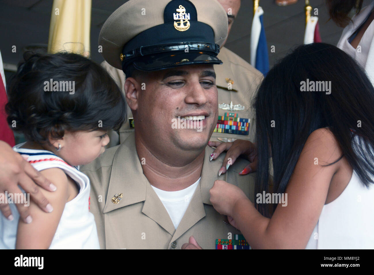 GARDEN CITY, New York (Sept. 15, 2017) Chief Navy Counselor Jhonan Mercado,  a native of New York and graduate of Cardinal Hayes High School, having his anchors pinned on his collar by his daughters during a chief petty officer pinning ceremony for Navy Recruiting District New York at the Cradle of Aviation Museum. (U.S. Navy photo by Mass Communication Specialist 1st Class Carlos M. Vazquez II/Released) - Stock Image