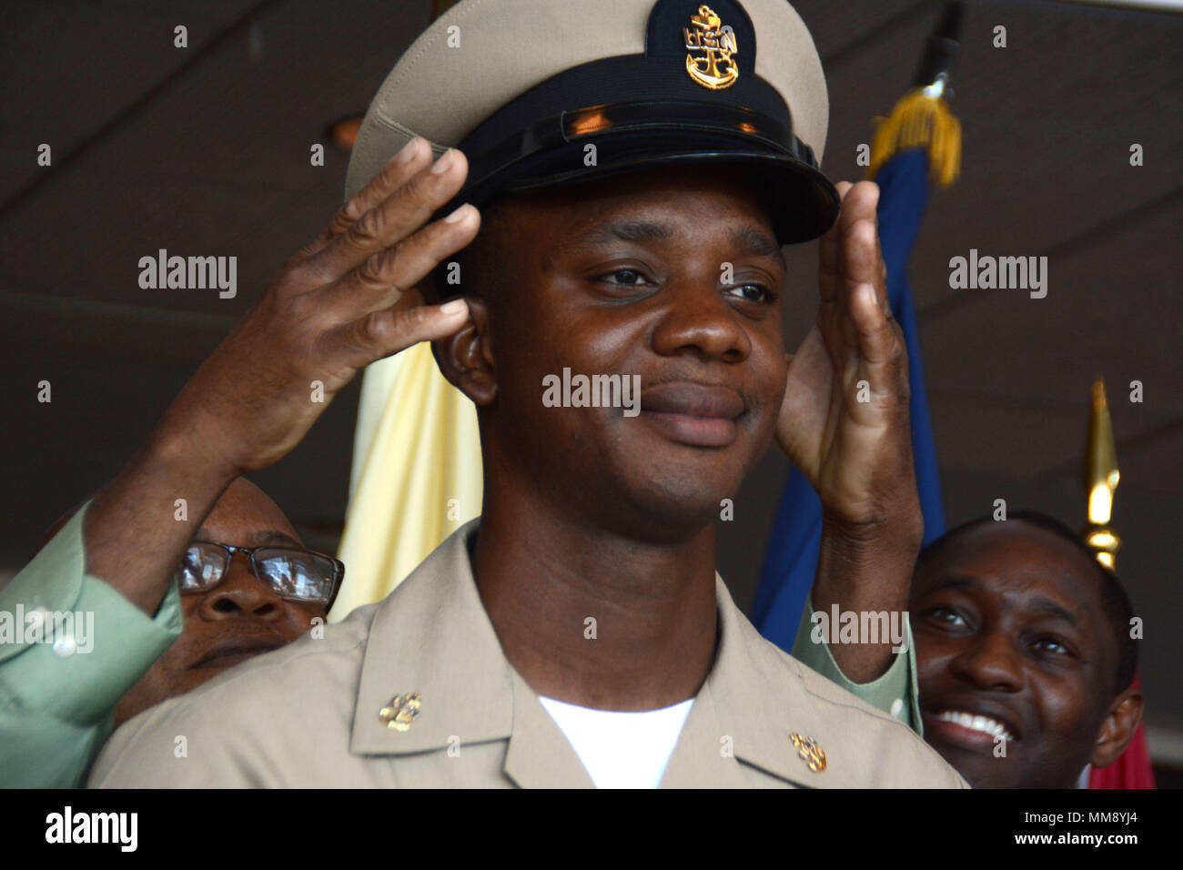 GARDEN CITY, New York (Sept. 15, 2017) Chief Boatswain's Mate Dwayne Todd, assigned to Navy Recruiting District New York and a native of Laurelton, New York, having his new cover donned on him by his father during a chief petty officer pinning ceremony at the Cradle of Aviation Museum. (U.S. Navy photo by Mass Communication Specialist 1st Class Carlos M. Vazquez II/Released) - Stock Image