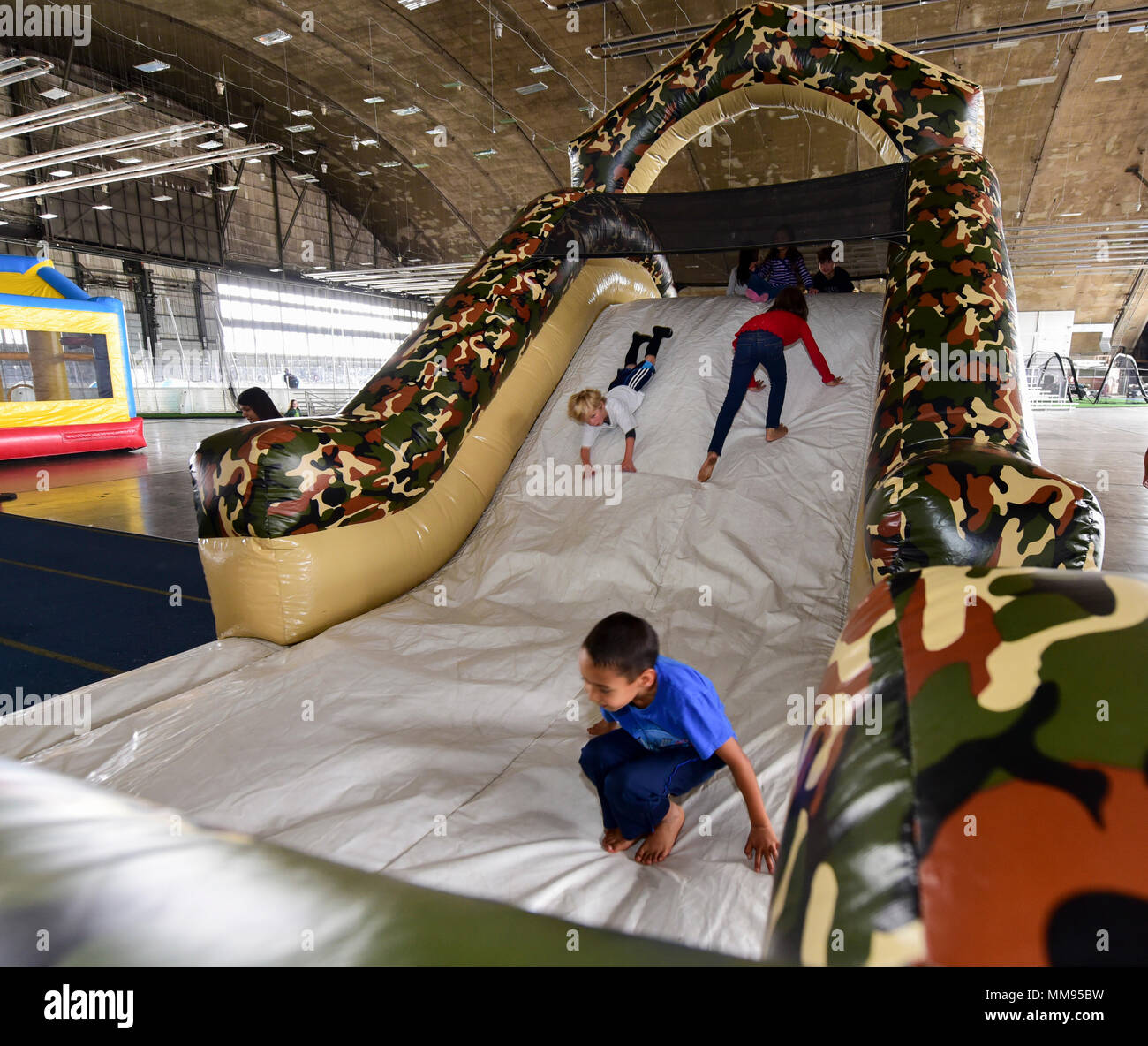 Children play on an inflatable obstacle course during a Base Appreciation Day at Ellsworth Air Force Base, S.D., Sept. 16, 2017. Activities at the event included bouncy castles, bean-bag toss and ladder ball. (U.S. Air Force photo by Airman 1st Class Randahl J. Jenson) - Stock Image