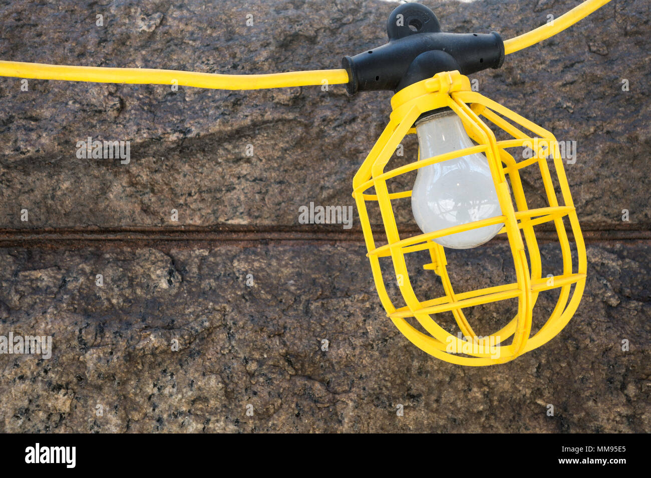 A yellow work light hanging outdoors on a wire - Stock Image