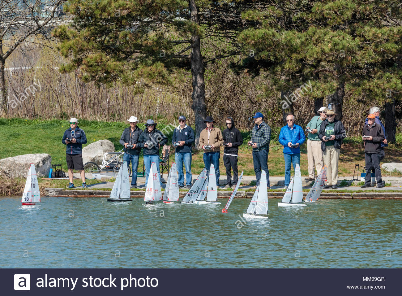 Men with radio controlled toy sailboats at Humber Park East in Toronto Ontario Canada - Stock Image