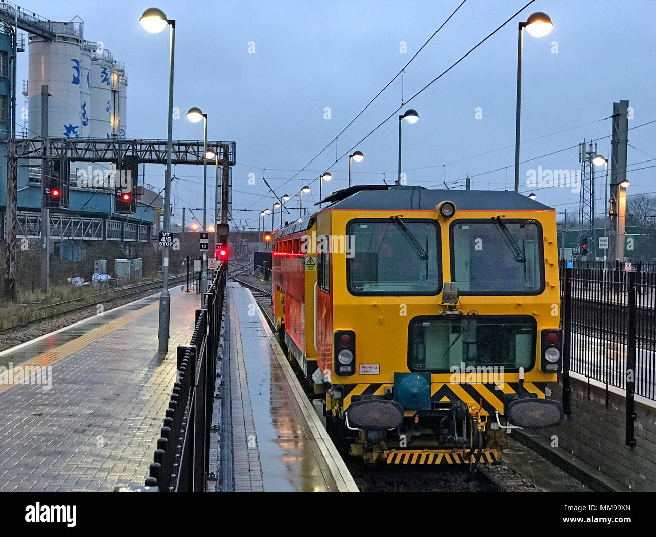 Railway track maintenance engine vehicle, Warrington Bank Quay station at dusk, Cheshire, England, UK, dusk, winter - Stock Image