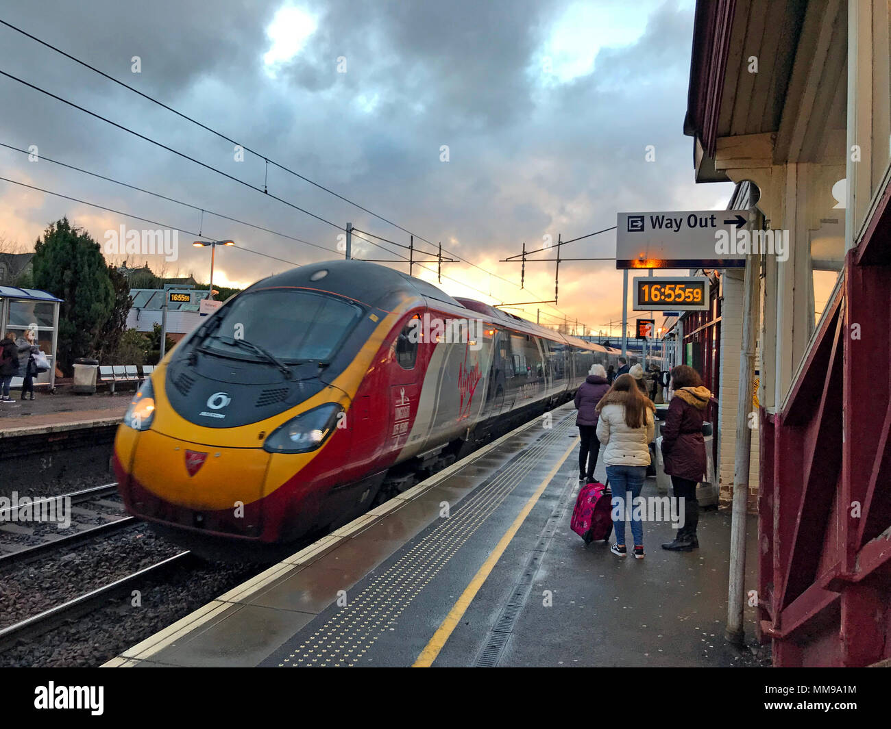 Virgin Pendolino arrives at Motherwell Railway Station, North Lanarkshire, Scotland at dusk, UK - Stock Image