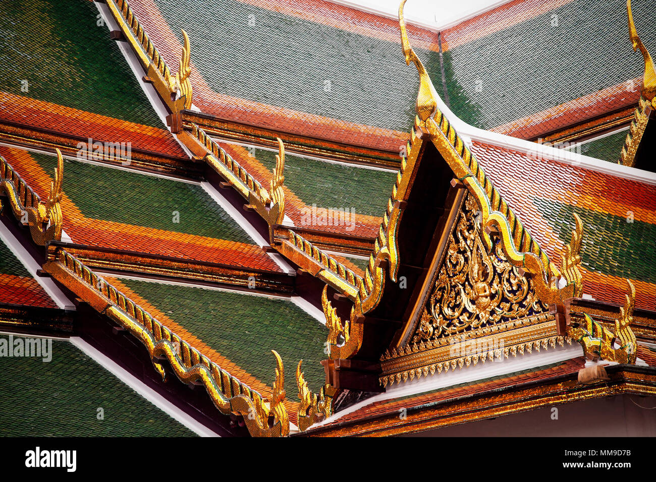 The tiled decorative roof of the Temple of the Emerald Buddha or Uboseth in the Grand Palace complex, Bangkok, Thailand. - Stock Image