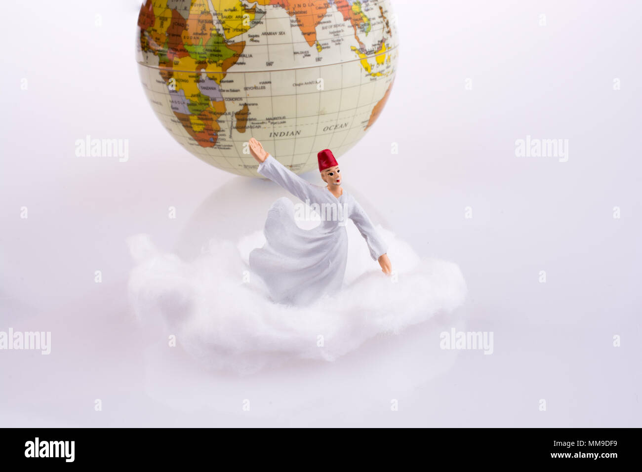 Sufi derviş on a white cloud near globe - Stock Image