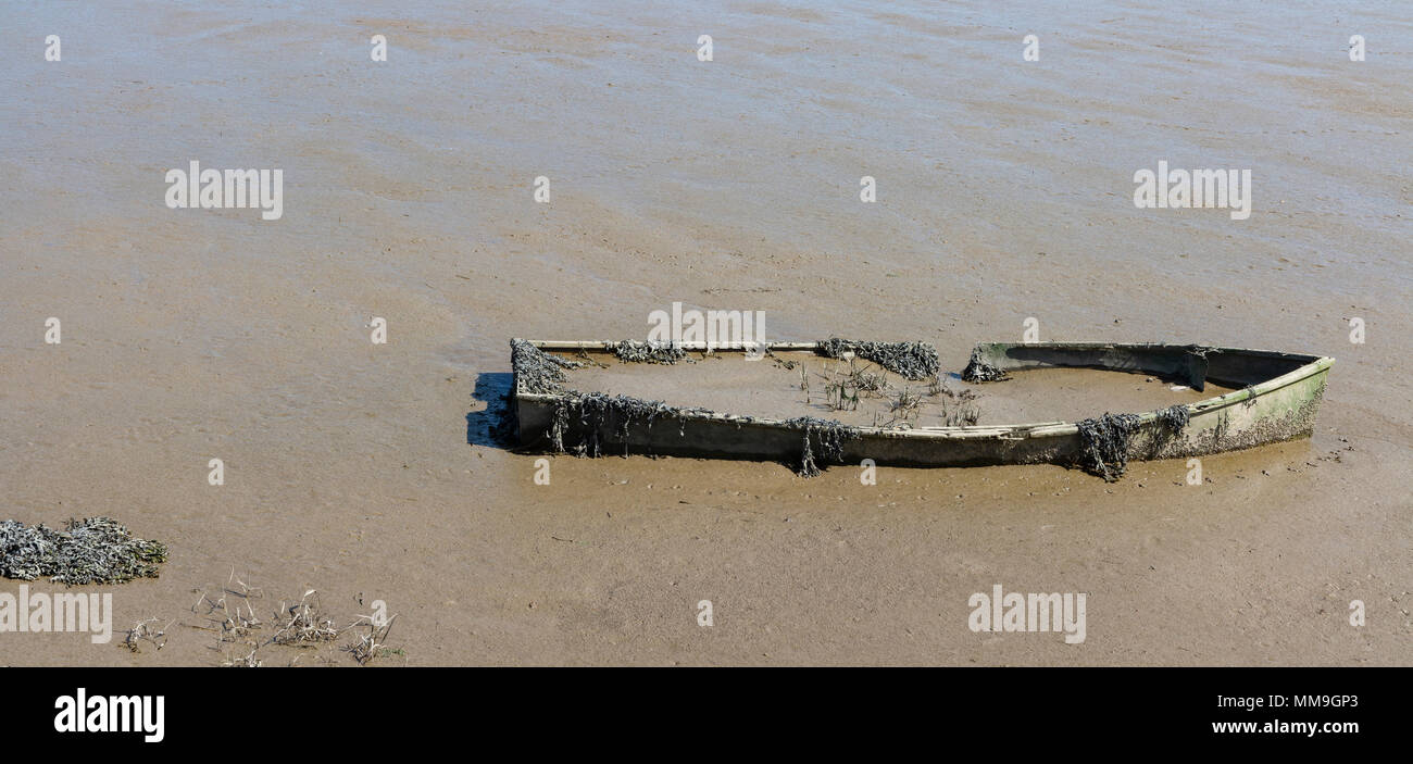 Sunken boat in Iken marshes and river Alde, Suffolk, England - Stock Image
