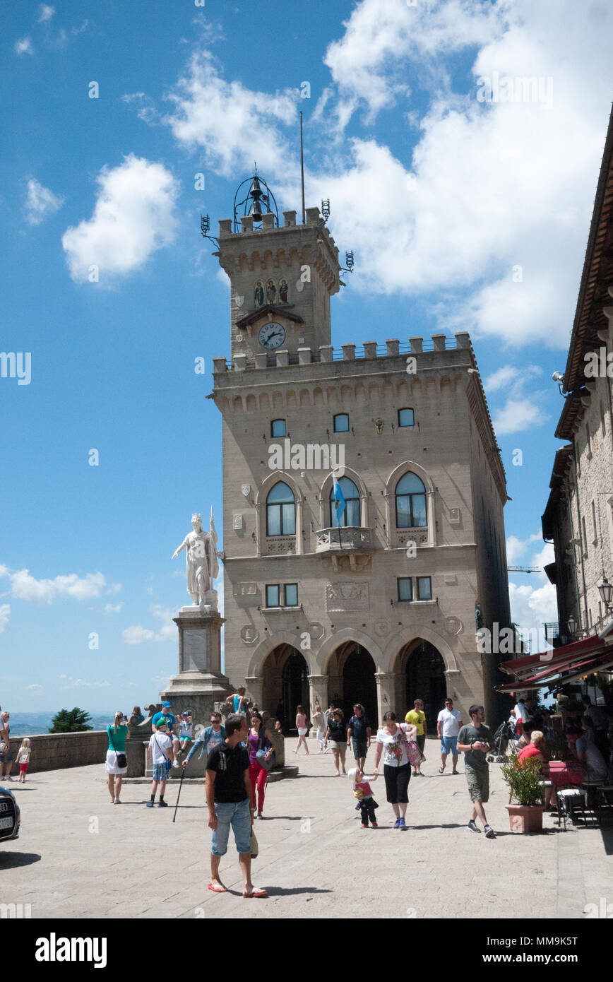 Tourists wander past the Palazzo Pubblico (Public Palace) town hall in the Republic of San Marino. - Stock Image