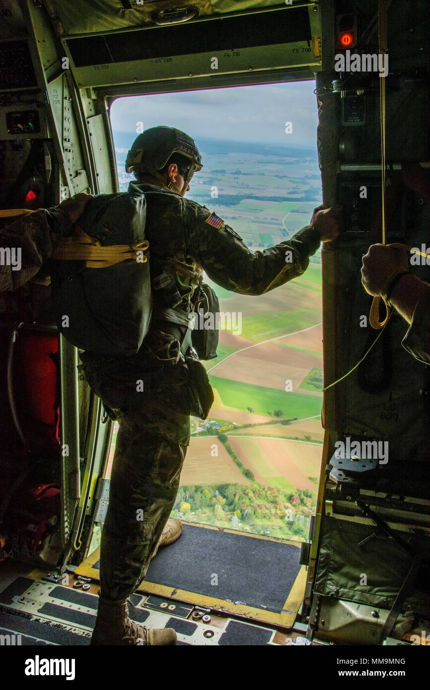A Jumpmaster assigned to 1st Battalion, 10th Special Forces Group (Airborne), looks out the door of a C-130 Hercules for a reference point during an airborne operation near Stuttgart, Germany, Sept. 20th, 2017. Jumpmasters use reference points to ensure they are on the correct flight path and to help determine the distance to their drop zone. The jump demonstrated Group's ability to lead airborne operations in the European theater. Airborne insertions are one of the many infiltration platforms available to Special Operations when responding to a crisis. (U.S. Army photo by Staff Sgt. Will Rein - Stock Image