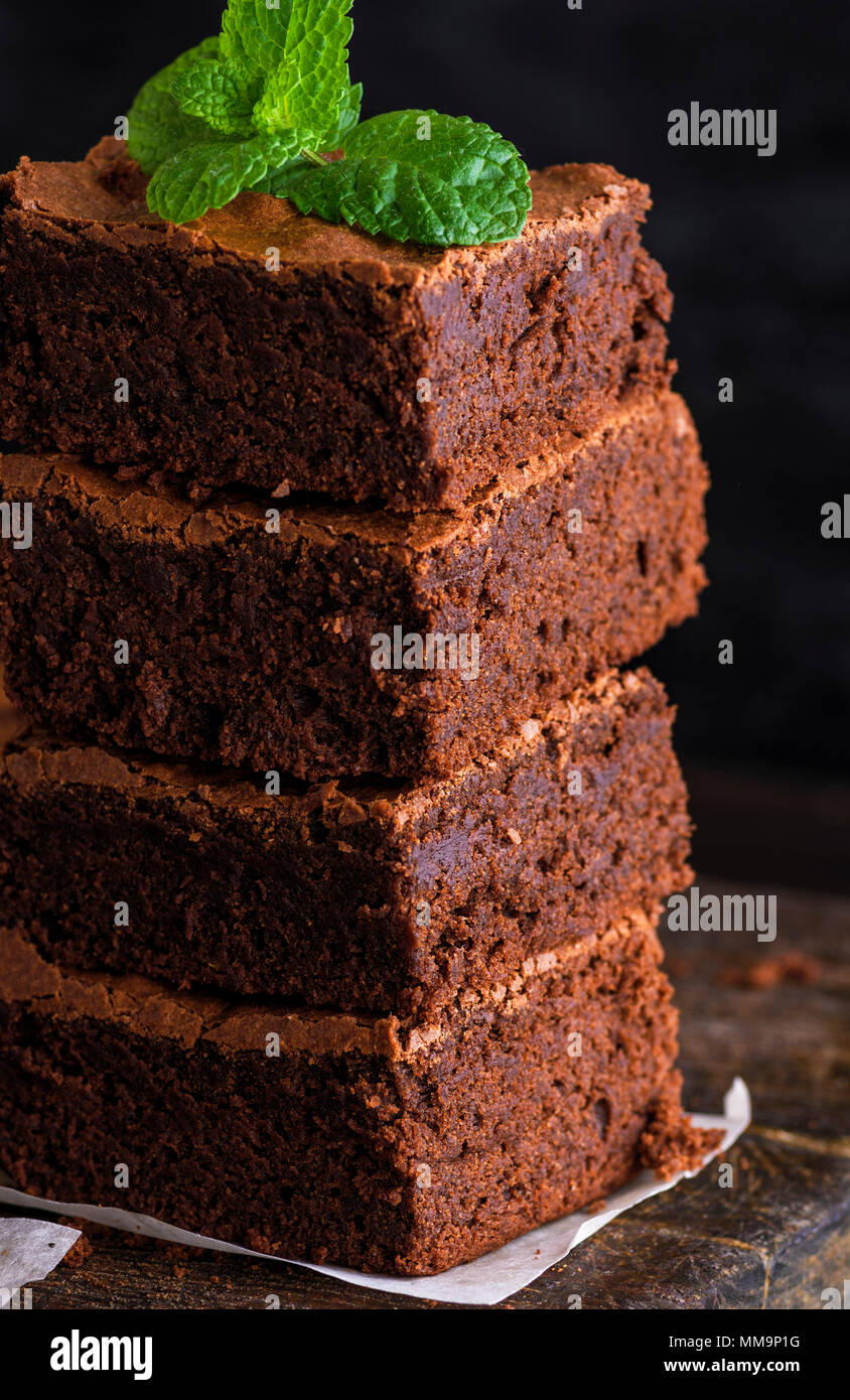 a pile of square pieces of brownie pie on a wooden surface, close up - Stock Image