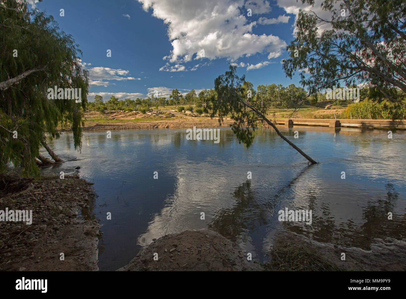 Landscape with Bowen River, with blue sky and clouds reflected in calm waters, hemmed with sandy bank and native trees in western Queensland Australia - Stock Image