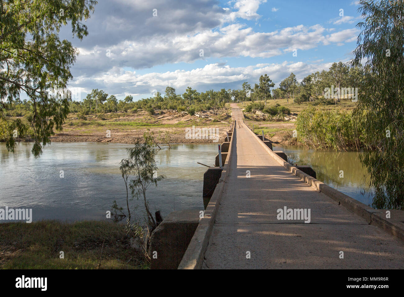 Long low narrow concrete bridge crossing calm waters of Bowen River with gravel road leading on through bushland under blue sky in Qld Australia - Stock Image