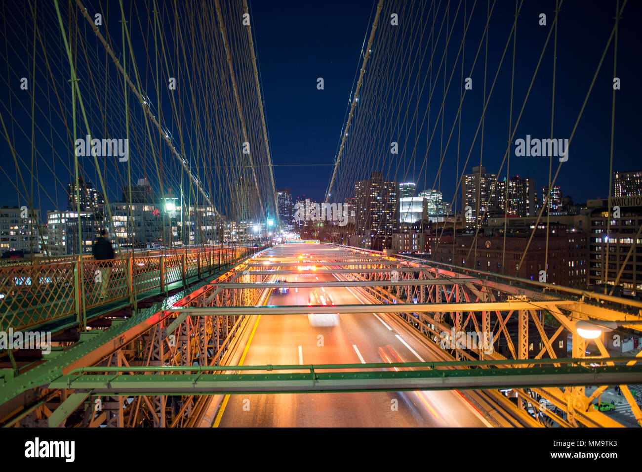 Long exposure picture of cars passing over the illuminated Brooklyn Bridge at night. Manhattan skyline in the background, New York city, USA. - Stock Image