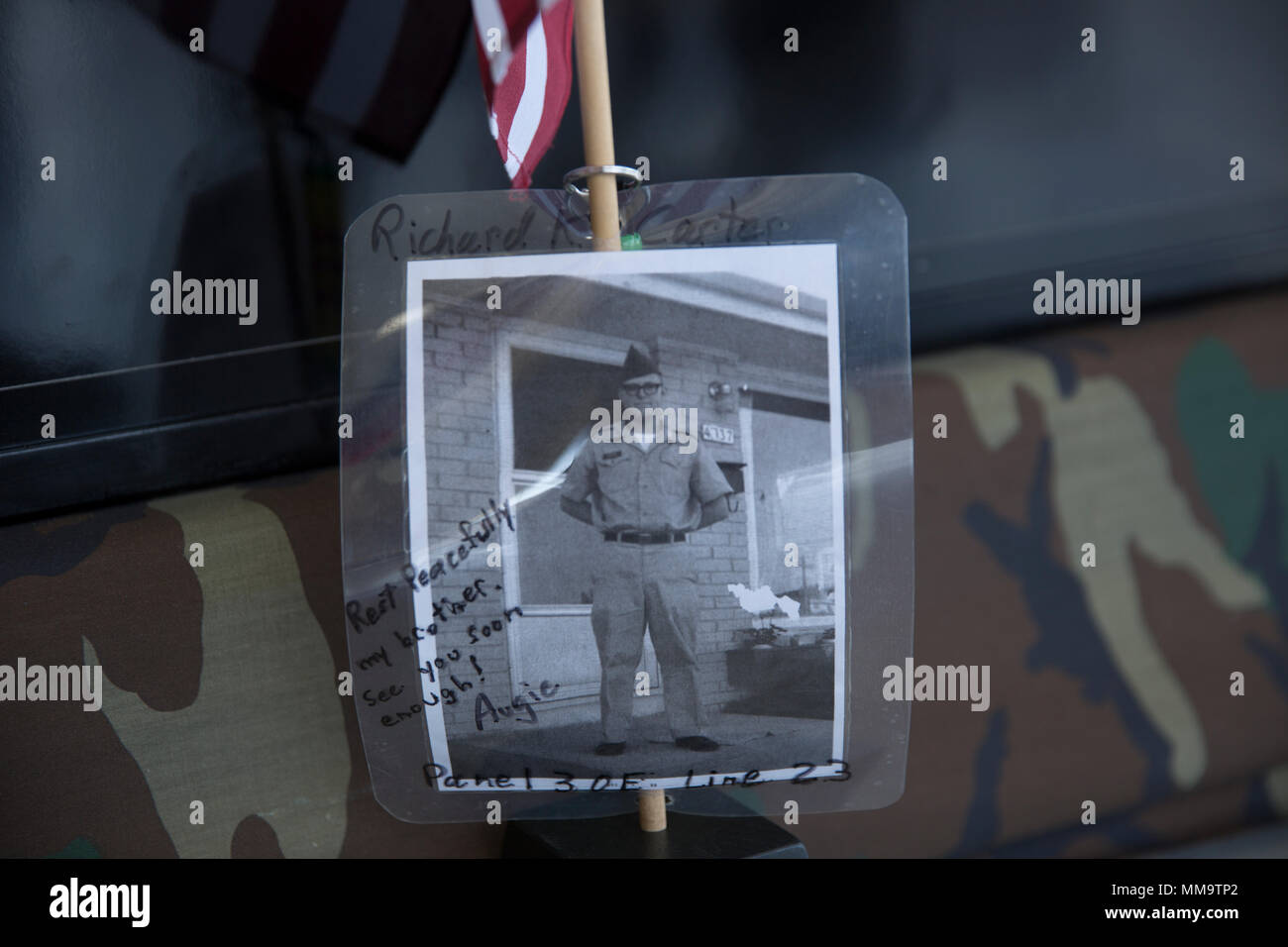 "A picture of Sgt. Richard Carter, a soldier who died during the Vietnam War, rests in front of the Mobile Vietnam Memorial Wall, also known as the AV Wall, during the 2017 Marine Corps Air Station Miramar Air Show at MCAS Miramar, Calif., Sept. 22. Carter's brother, Augie Anderson, is an AV Wall volunteer and placed the flag and photograph as a way to remember Carter, who died Nov. 19, 1967.  Anderson wrote ""Rest peacefully my brother, see you soon enough!"" (U.S. Marine Corps photo by Sgt. Lillian Stephens/Released) - Stock Image"