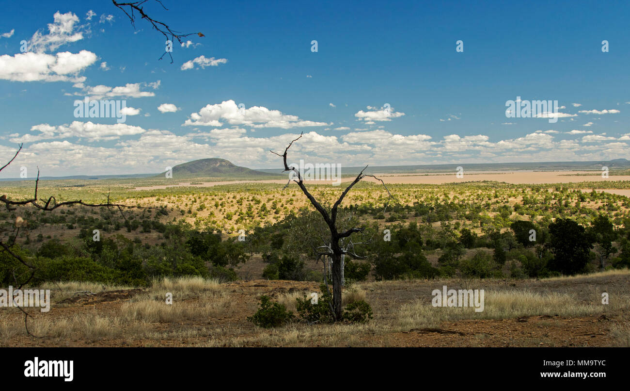 Spectacular landscape with wooded islands rising from waters of immense lake formed by Burdekin Falls dam & hemmed by trees under blue sky, Australia Stock Photo