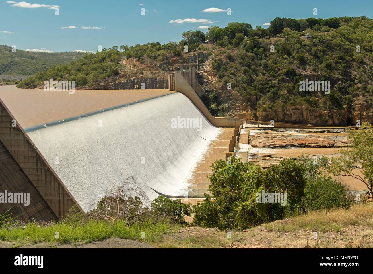 Burdekin Falls dam with high spillway overflowing and coffee coloured water flowing into rocky river bordered by wooded hills under blue sky, Qld Aust - Stock Image