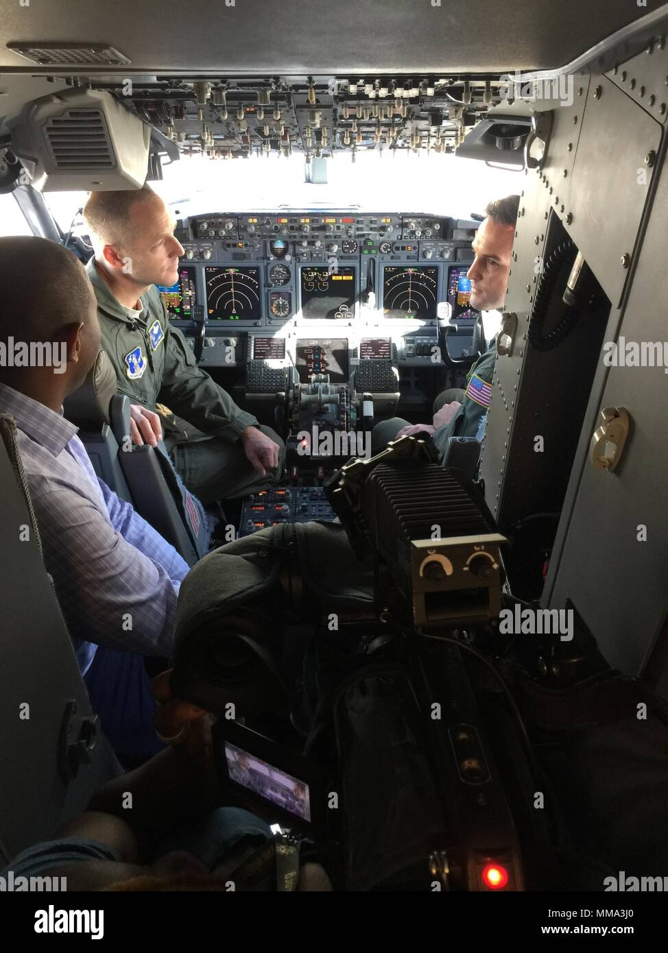 201st Airlift Squadron pilots Maj. Greg Boney (left) and Capt. Brandon Splawn (right) speak to reporters on the C-40 Clipper, aircraft flight deck at Joint base Andrews, Md., Sept. 27, 2017. The pilots, two inflight passenger specialists and two flight crew chiefs operated the aircraft carrying 10 Metropolitan Police Department of the District of Columbia Officers, and 3,000 lbs. of supplies, to Puerto Rico to aide in hurricane Maria relief efforts. (U.S. Air National Guard Photo by Senior Master Sgt. Craig Clapper/released) - Stock Image