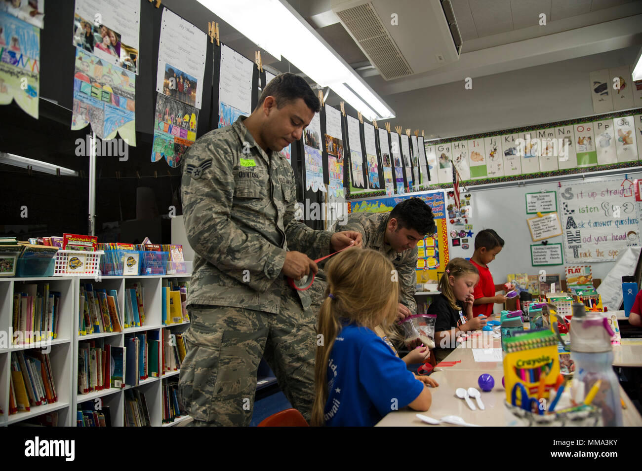 Senior Airman Francisco Quintana and Senior Airman Eddy Santibanez, 647th Logistics Readiness Squadron combat mobility team members, help second grade students make maracas at Hickam Elementary School, Joint Base Pearl Harbor-Hickam, Hawaii, Sept. 27, 2017.  Volunteers organized a variety of events for the students in support of Hispanic Heritage Month.  Hispanic Heritage Month is observed from 15 Sept.-15 Oct. to celebrate the history, culture and contributions of American citizens whose ancestors came from Spain, Mexico, the Caribbean and Central and South America. (U.S. Air Force photo by T - Stock Image