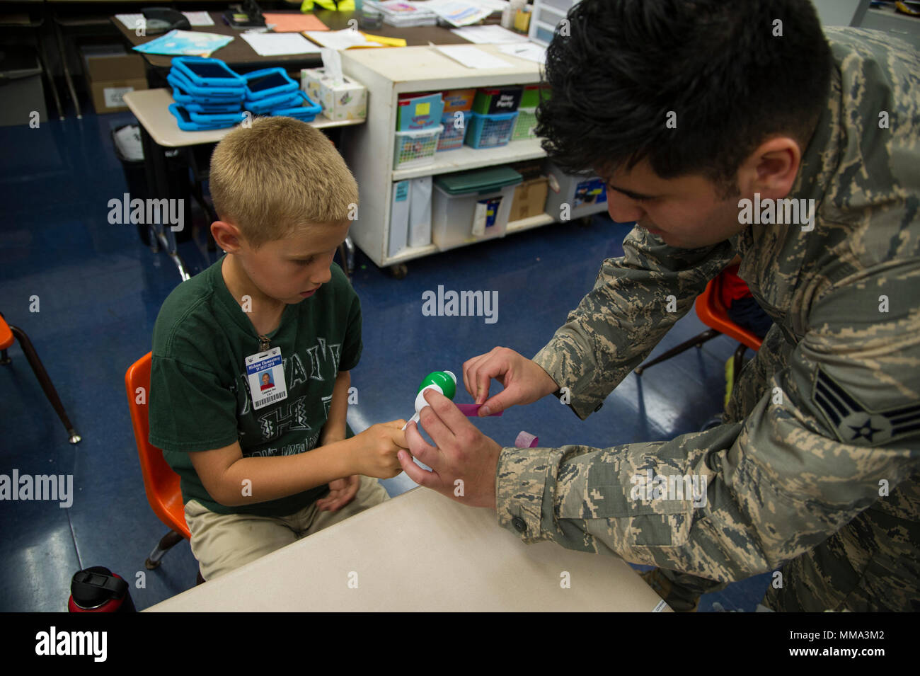 Senior Airman Eddy Santibanez, 647th Logistics Readiness Squadron combat mobility team member, helps second grade students make maracas at Hickam Elementary School, Joint Base Pearl Harbor-Hickam, Hawaii, Sept. 27, 2017.  Volunteers organized a variety of events for the students in support of Hispanic Heritage Month.  Hispanic Heritage Month is observed from 15 Sept.-15 Oct. to celebrate the history, culture and contributions of American citizens whose ancestors came from Spain, Mexico, the Caribbean and Central and South America. (U.S. Air Force photo by Tech. Sgt. Heather Redman) - Stock Image