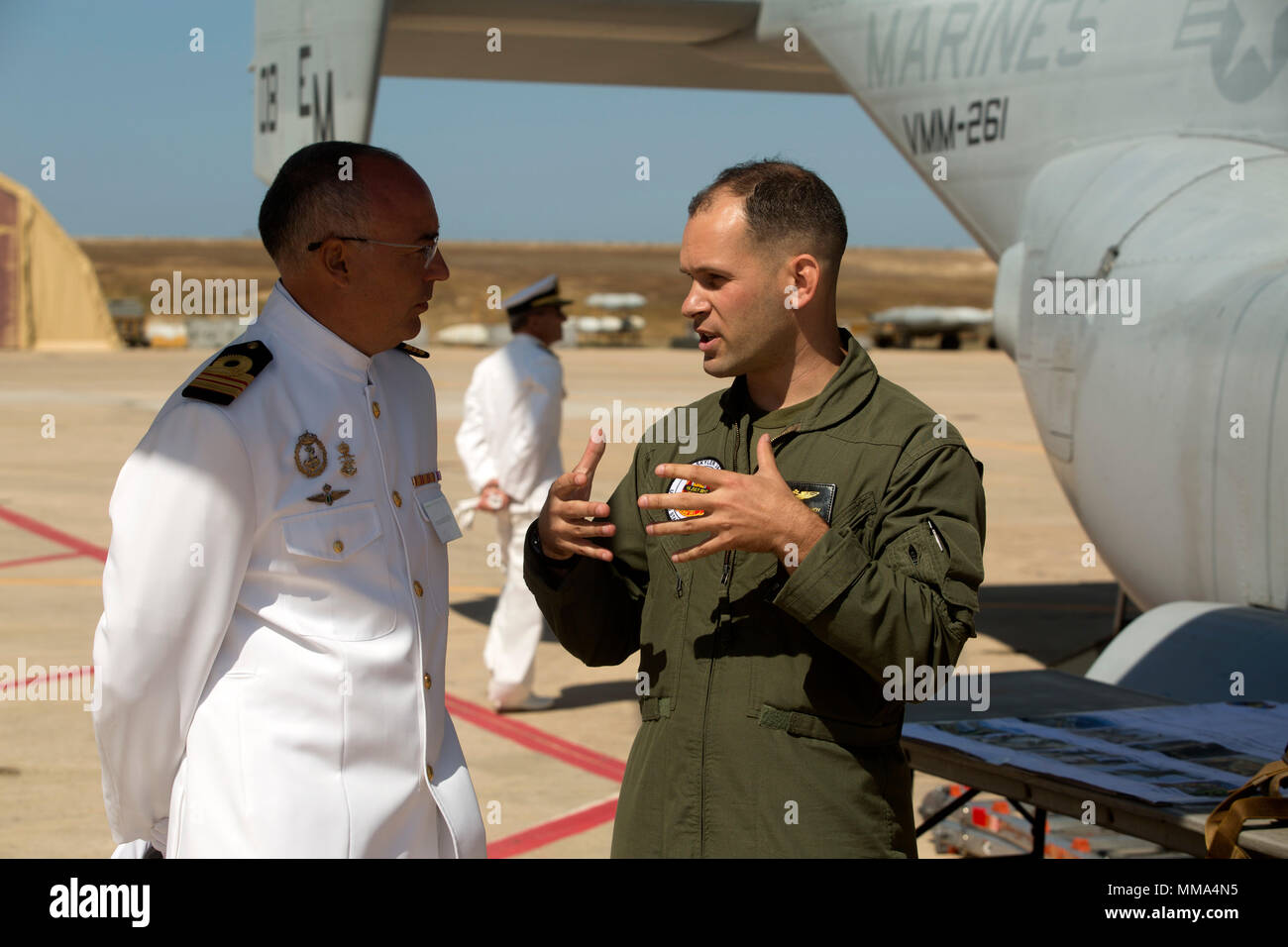 Captain Jonathan D. Hoy, an MV-22B Osprey pilot with Special Purpose Marine Air-Ground Task force-Crisis Response-Africa aviation combat element, speaks with a member of the Spanish Navy about the Osprey's capabilities during the Spanish military's airshow at Naval Station Rota, Spain, Sept. 15, 2017. The airshow commemorated the 100-year anniversary of Spanish aviation. (U.S. Marine Corps Photo by SSgt. Kenneth K. Trotter Jr. - Stock Image