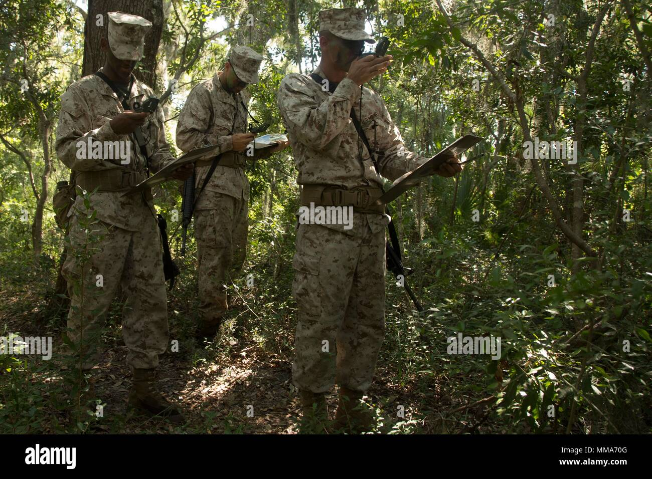 U.S. Marine Corps Recruits with Delta Company, 1st Battalion, Recruit Training Regiment, use compass techniques to reach their next plot point at Elliot's Beach on Marine Corps Recruit Depot, Parris Island, S.C., Sept. 25, 2017.  The Land Navigation Course teaches recruits how to properly navigate unfamiliar terrain.  (U.S. Marine Corps photo by Lance Cpl. Yamil Casarreal/Released) Stock Photo