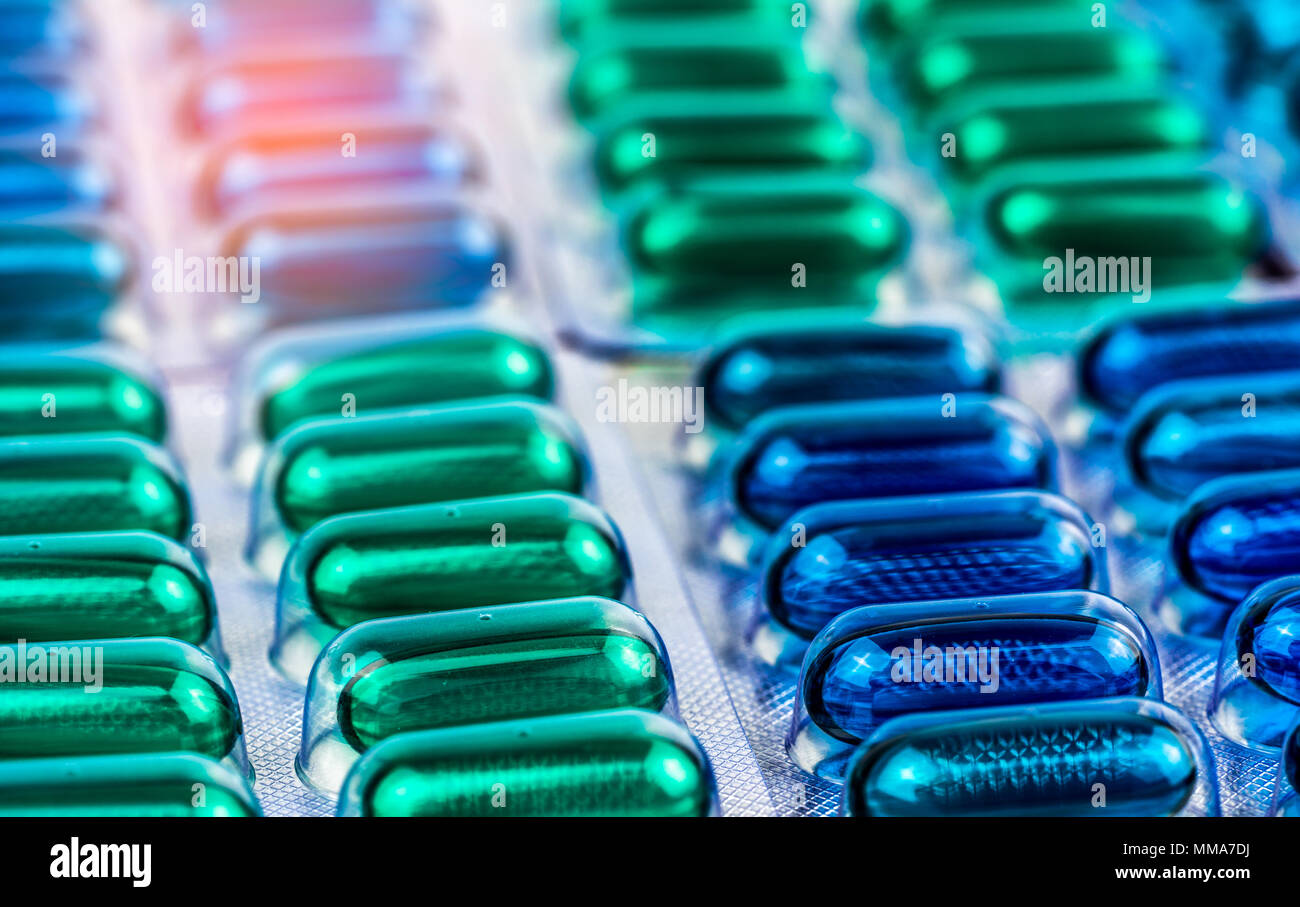 Selective focus on blue and green soft gel capsule pills in blister pack. Naproxen and ibuprofen (Nonsteroidal anti-inflammatory drugs) : Painkiller m - Stock Image