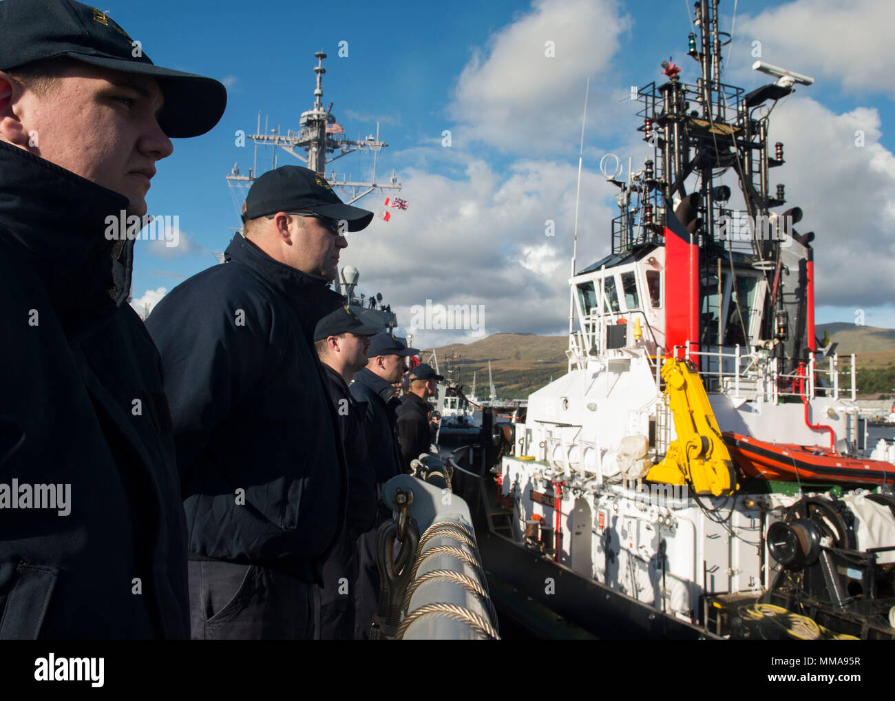170921-N-UB406-445 FASLANE, Scotland (Sept. 21, 2017) Sailors assigned to the Arleigh Burke-class guided-missile destroyer USS Mitscher (DDG 57) man the rails as the ship arrives at Her Majesty's Naval Base  Clyde in Scotland, Sept. 21, 2017. Mitscher, homeported in Norfolk, is conducting naval operations in the U.S. 6th Fleet area of operations in support of U.S. national security interests in Europe. (U.S. Navy photo by Mass Communication Specialist Seaman Cameron M. Stoner/Released) - Stock Image