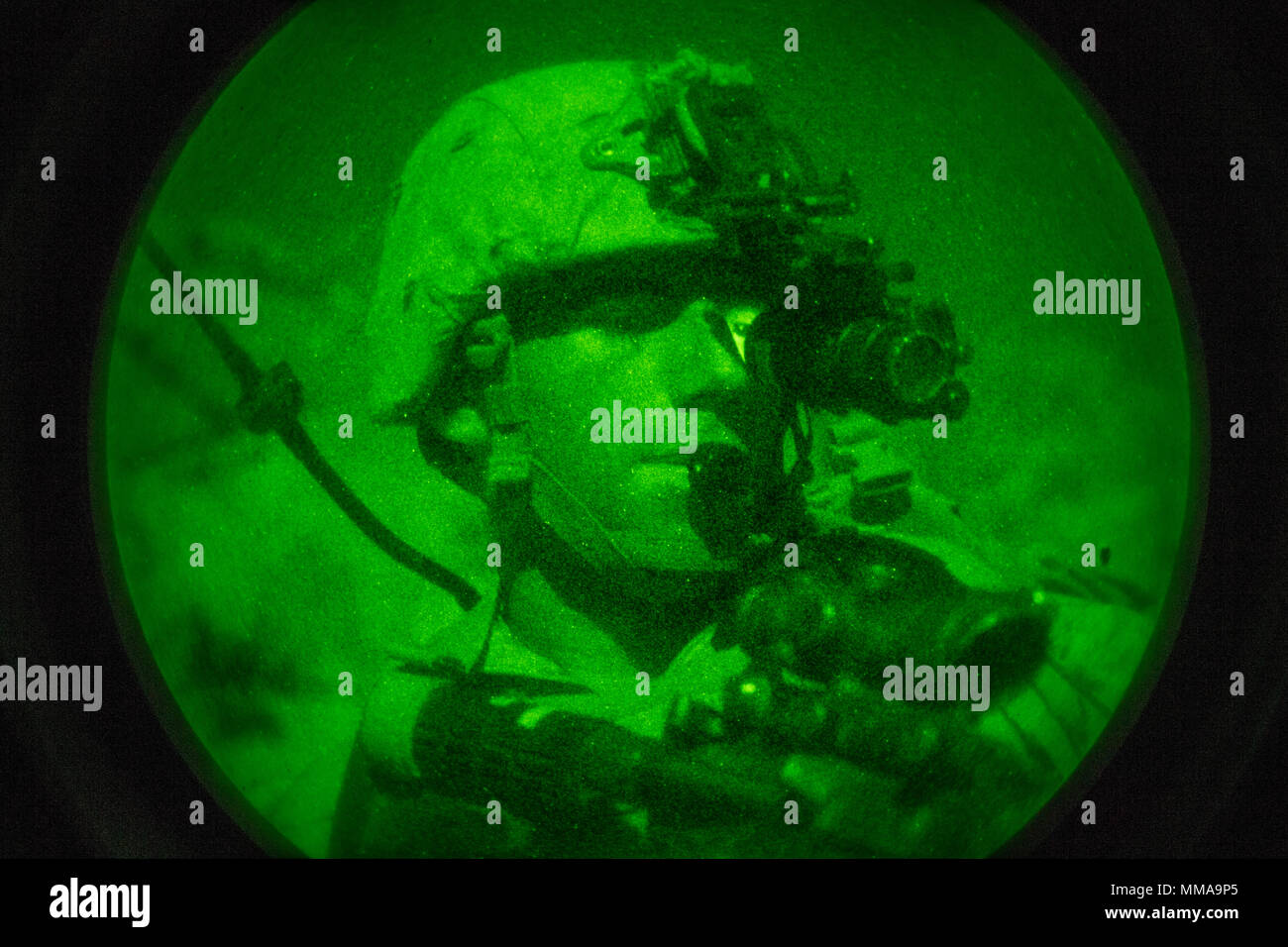 A U.S. Marine with Regimental Surveillance & Target Acquisition Company (RSTAC), 1st Marine Division, looks through a PVS-14 night vision scope during a night insert at Fort Irwin, Calif., Oct. 1, 2017. RSTAC is an experimental company designed to build proficiency in scout sniper operations for service level exercises. (U.S. Marine Corps photo by Lance Cpl. Alexa M. Hernandez) Stock Photo