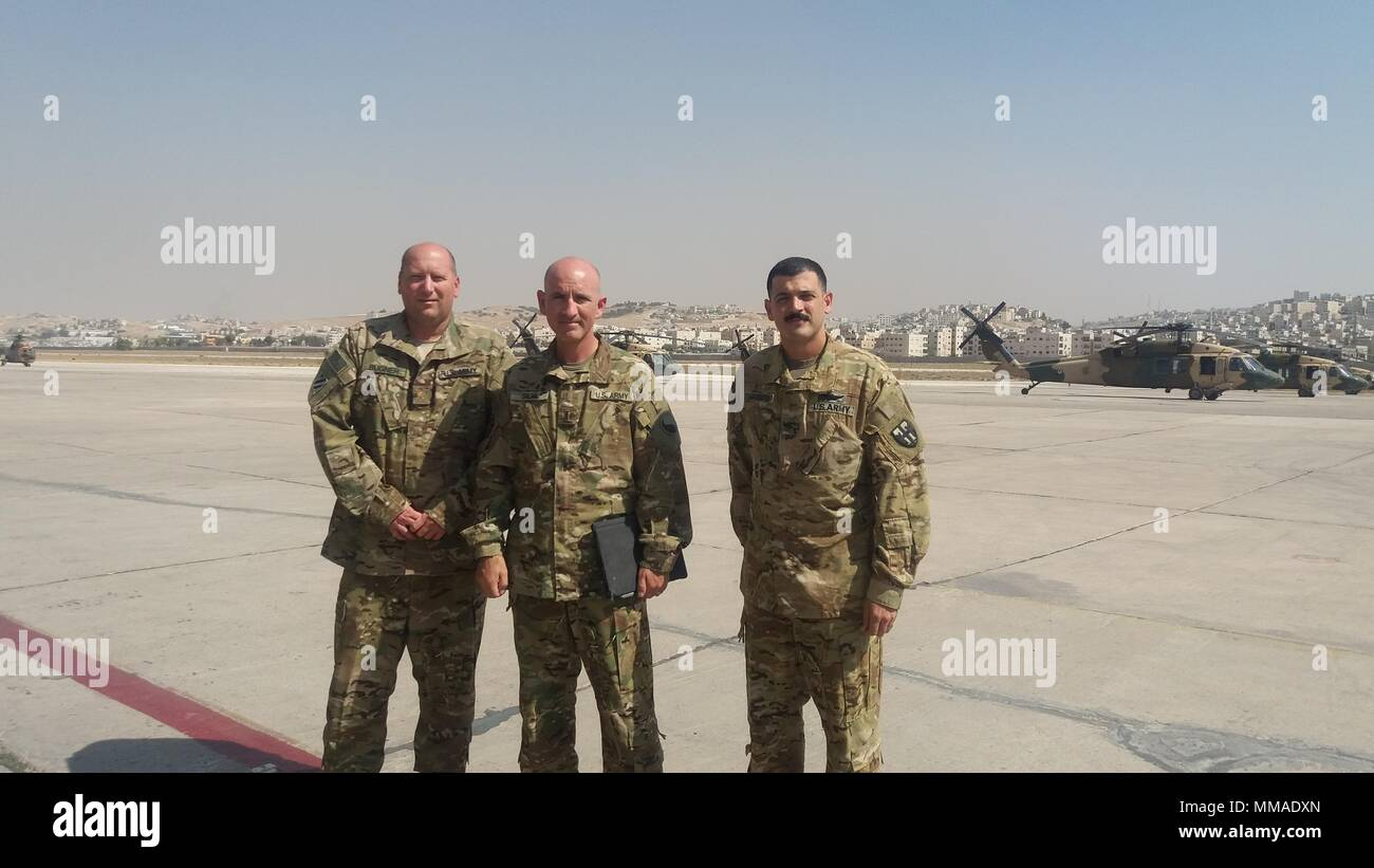 Maj. Robert Bugner (left), Chief Warrant Officer 4 John Silva (center) and Chief Warrant Officer 2 Melvin Marrero-Acevedo (right), pose for a photo in front of a Royal Jordanian Air Force Squadron 8 UH-60 Black Hawk helicopters at Amman, Jordan, Sept. 12. Soldiers from the 29th Combat Aviation Brigade participated in a power management and hoist maintenance expert exchange designed to increase the interoperability of both U.S. and Jordanian forces.   (Courtesy photo) - Stock Image