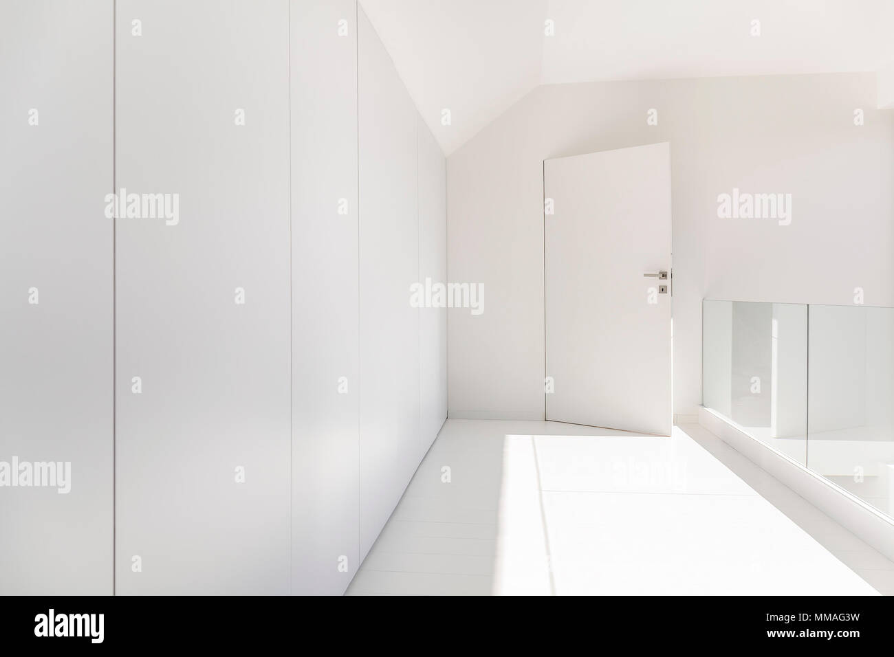 White home interior with mirror and open doors Stock Photo