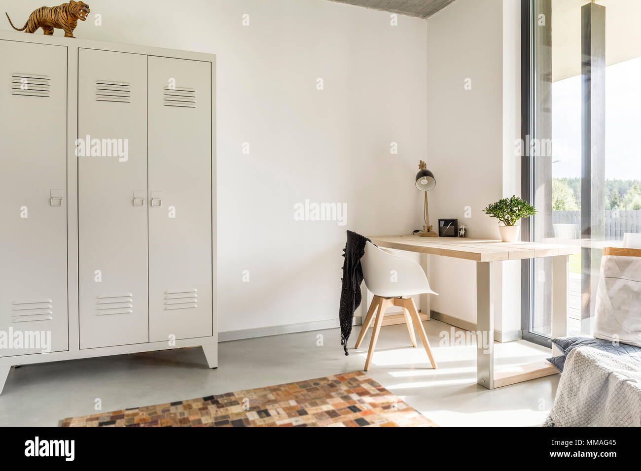 White home interior with metal wardrobe, desk and chair Stock Photo