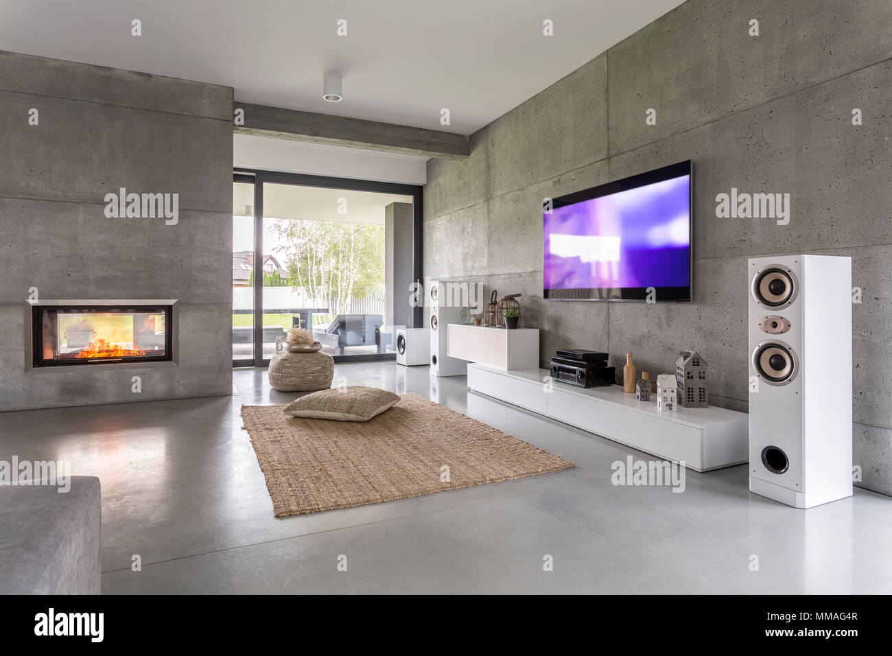 Tv living room with window, fireplace and concrete wall effect Stock Photo