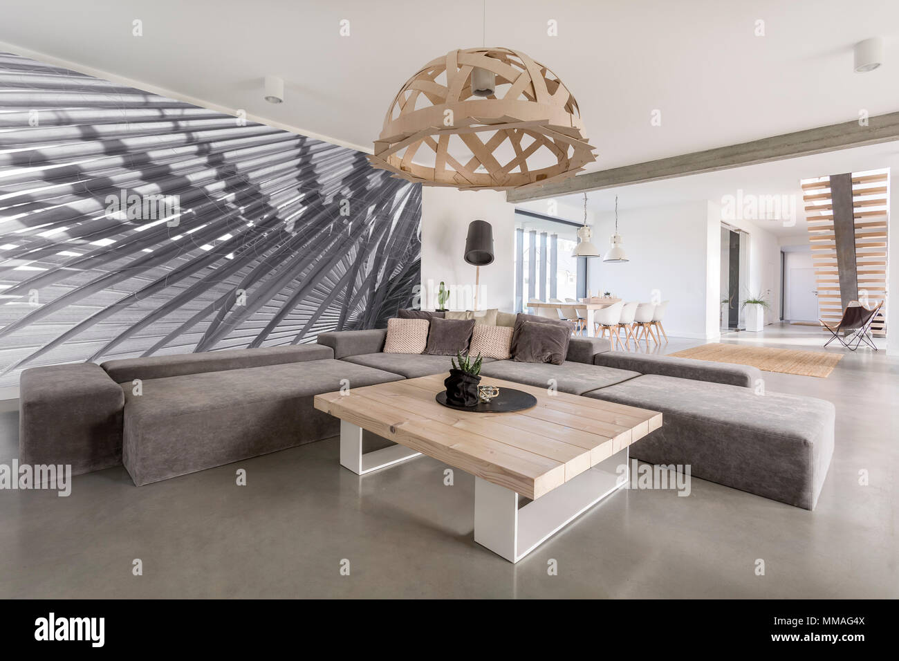 Room with extra large sofa, wooden table and photo wallpaper Stock Photo