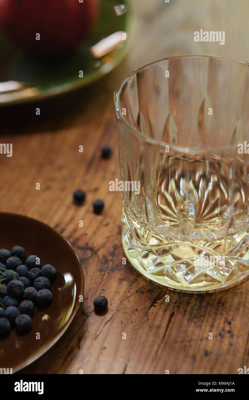 A glass of gin with juniper berries (Juniperus Communis) on a rustic table - Stock Image